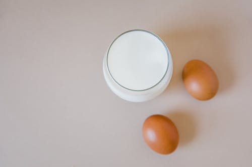 Close-Up Shot of a Glass of Milk beside Two Eggs