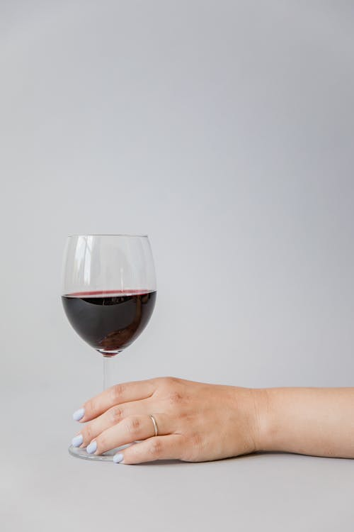 Close-Up Shot of a Person Holding a Glass of Red Wine