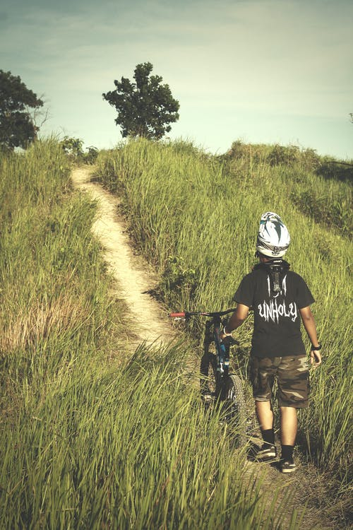 Мужчина в черной рубашке и коричневых шортах держит велосипед