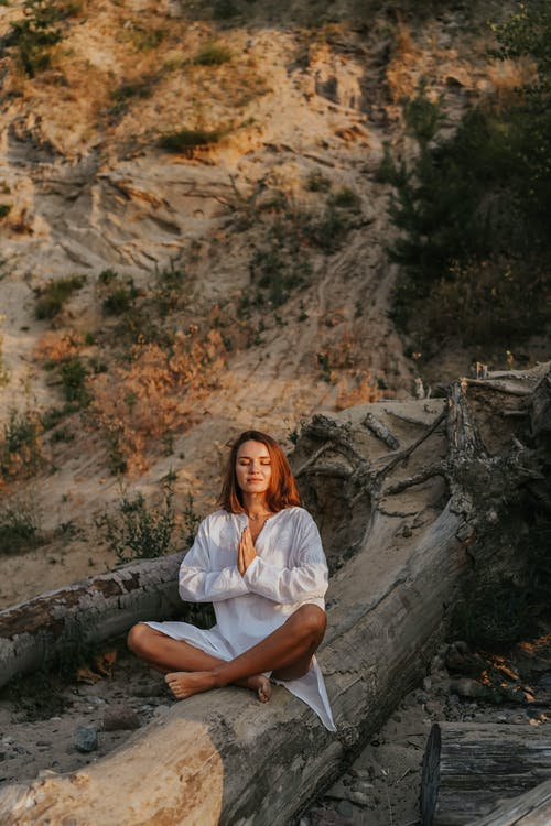 Woman in White Button Up Shirt Sitting on Rock