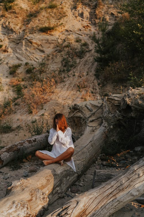 A Woman Meditating on a Tree Trunk