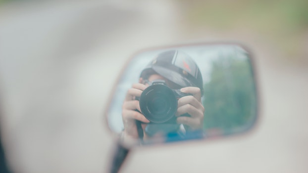 Shallow Focus Photography of Person Holding Dslr Camera in Mirror Reflection