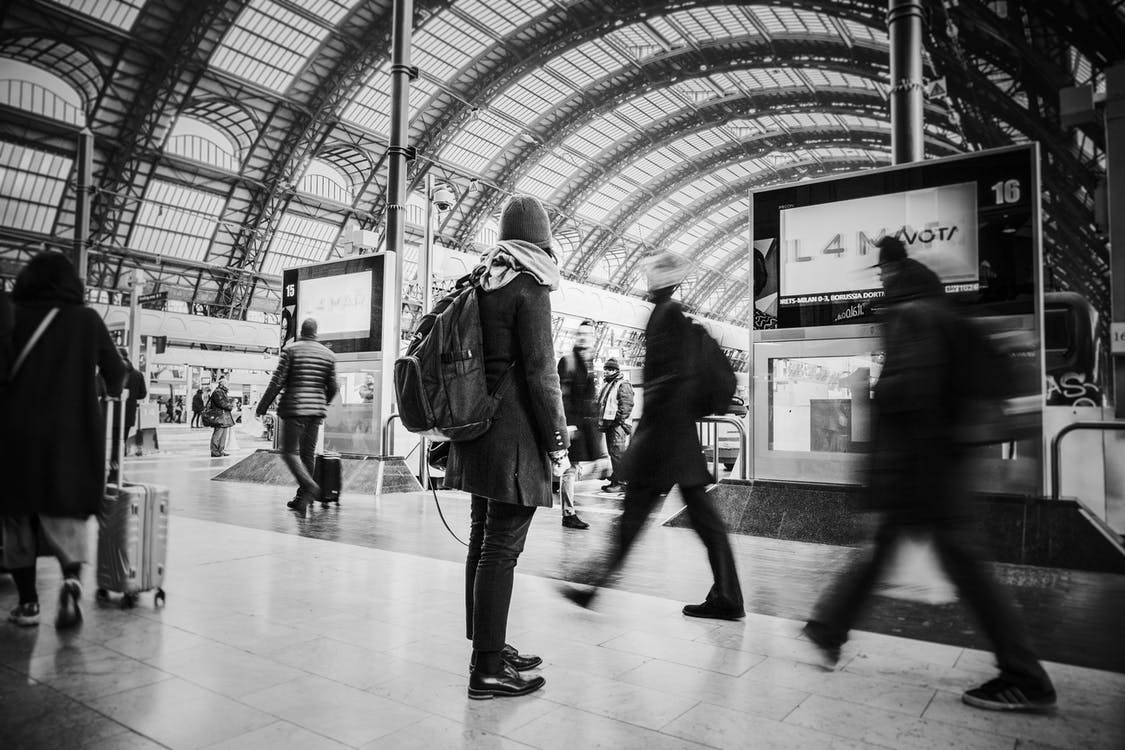 Time Lapse Grayscale Photograph of People Pass Through Inside Transportation Terminal