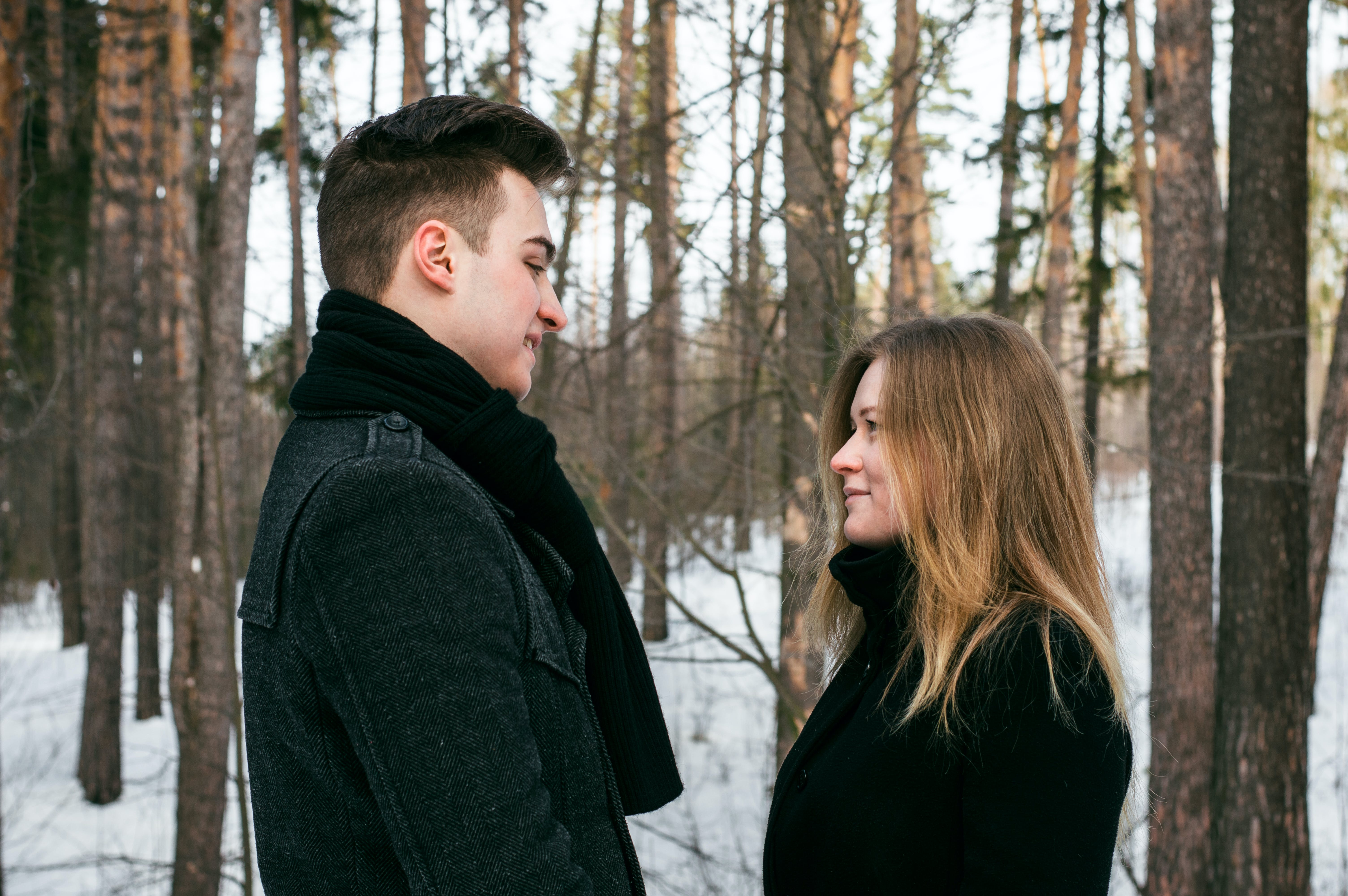 Man and Woman Wearing Black Coats Standing Near Snow-covered Trees