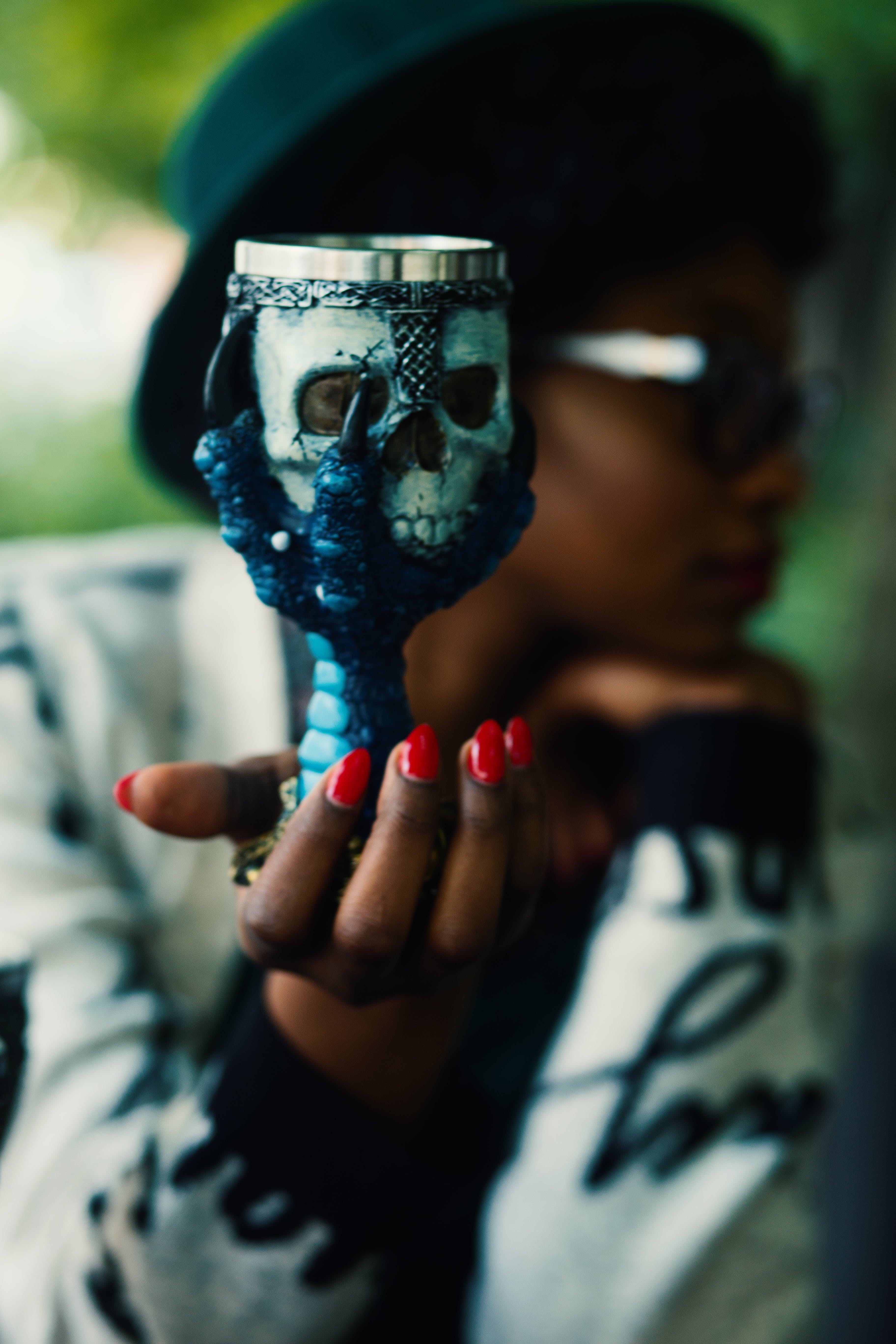 Person Holding Skull and Bird Claw Goblet
