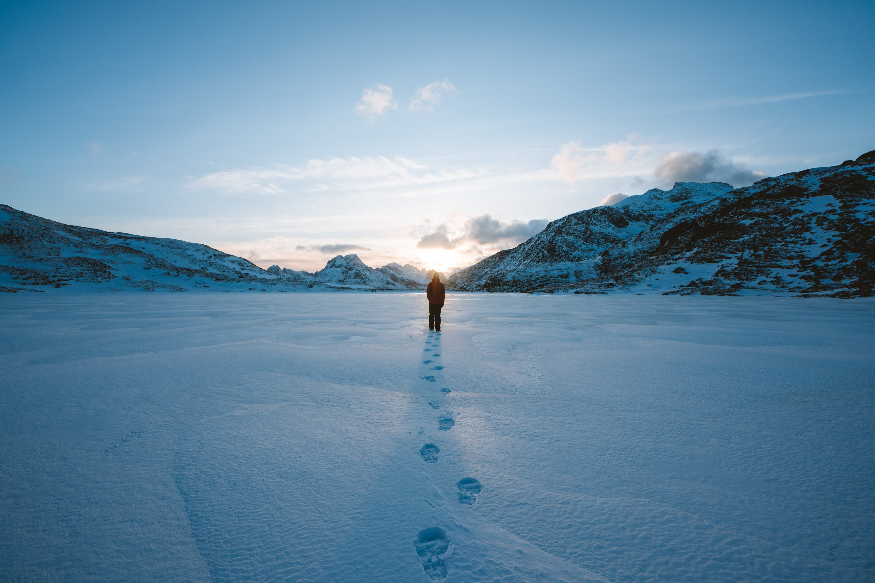 Person Walking in Snow Field Near Mountain Cliff Covered With Snow