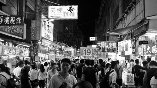Grayscale Photo of People Walking on a Marketplace