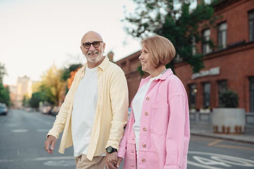 Happy Elderly Couple Holding Hands while Walking on the Street