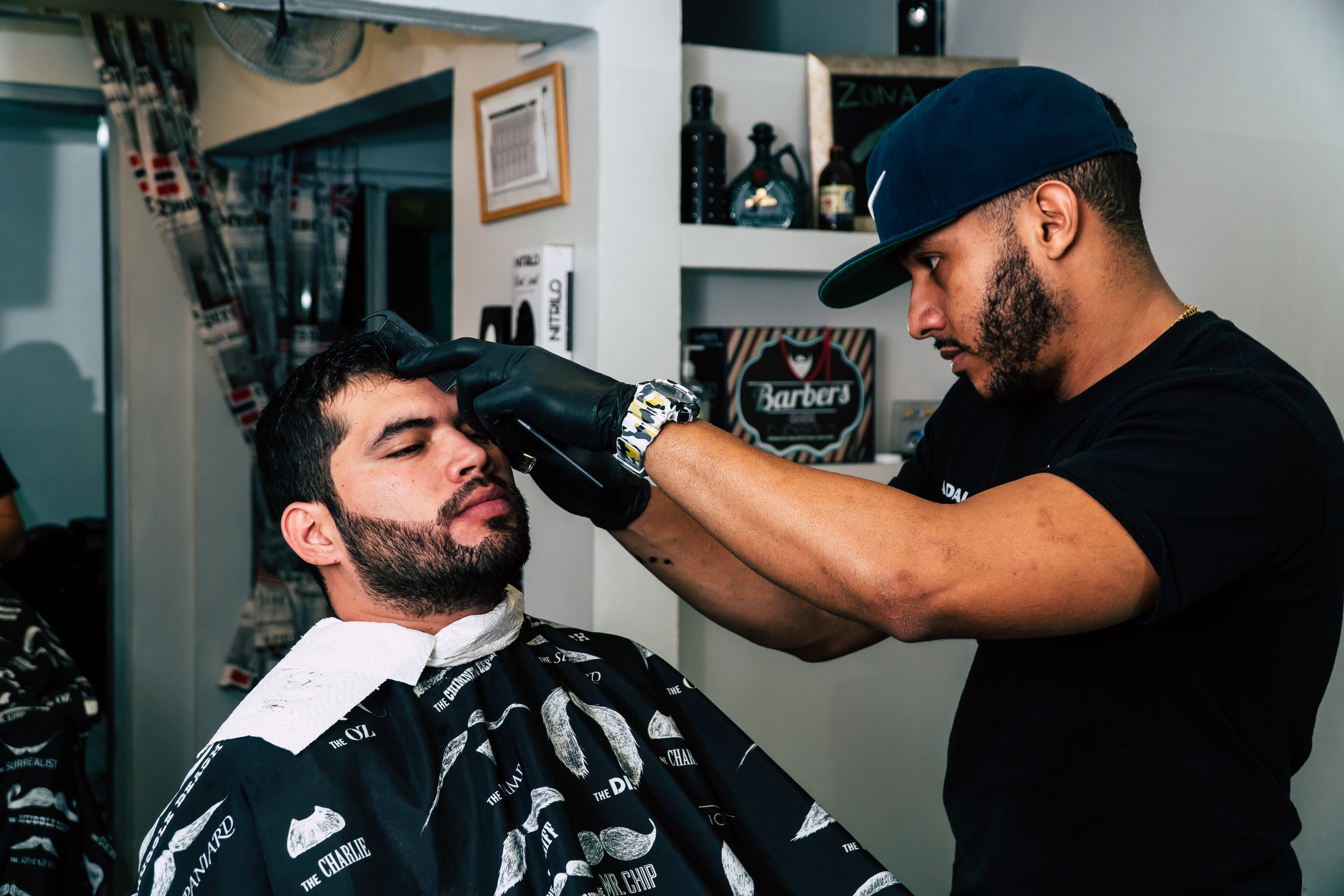 Man Wearing Black Shirt Trimming the Hair of Man
