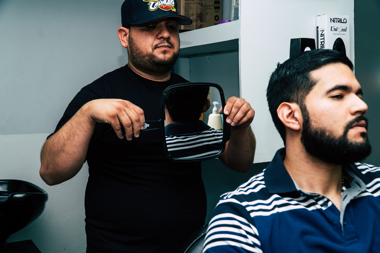 Man Holding Mirror Behind Man