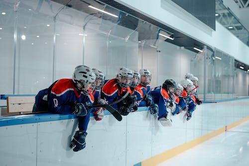 Ice Hockey Players In Orange and Blue Uniform