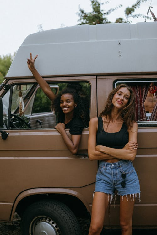 Woman in Black Tank Top and Blue Denim Shorts Sitting on White Car