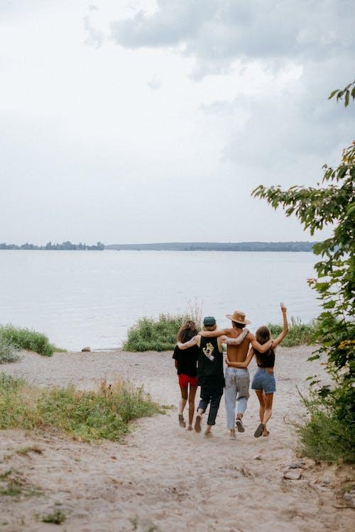 3 Women and 2 Men Standing on Green Grass Field Near Body of Water