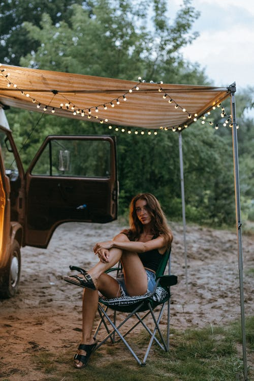 Woman in Black Tank Top Sitting on Blue and Black Camping Chair Beside Brown Car during