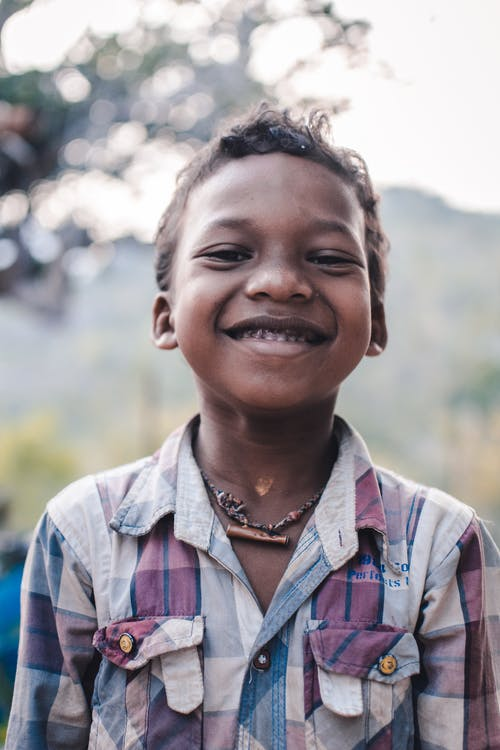 Smiling Boy in Blue White and Brown Plaid Button Up Shirt