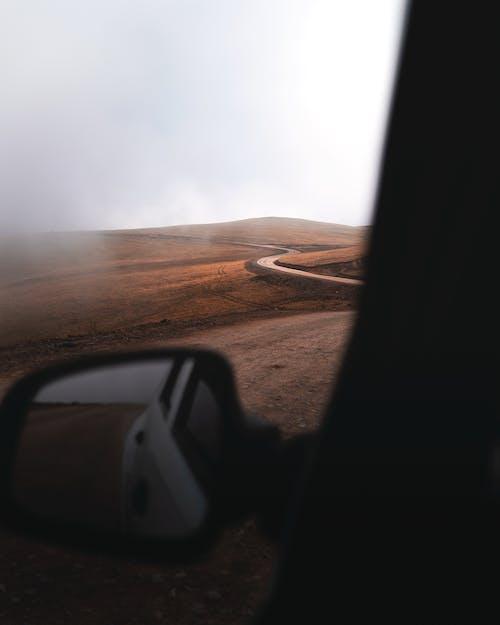 Free stock photo of car, foggy landscape, mountain path