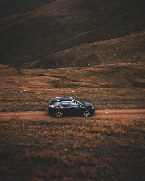 Black Sedan on Brown Field