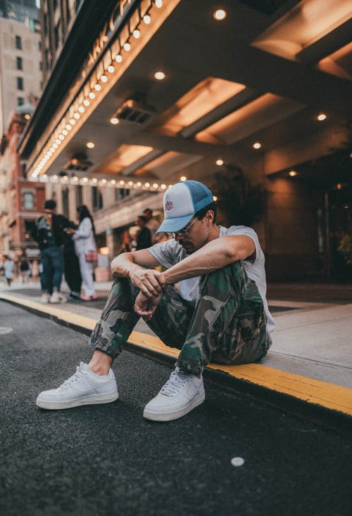 Man in Army Pants Sitting on Pavement