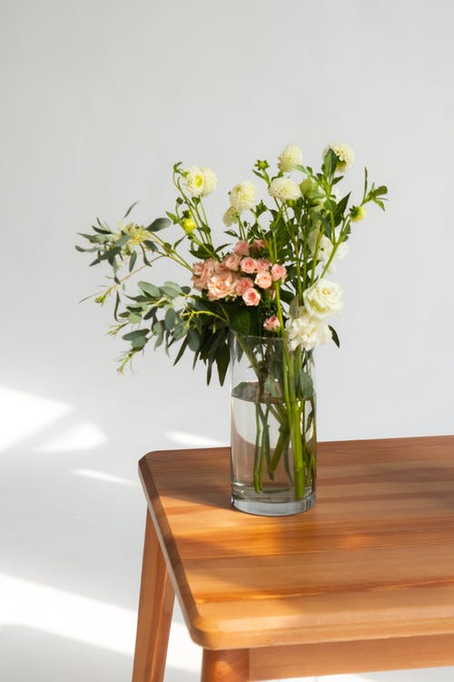 Yellow and White Flowers in Clear Glass Vase on Brown Wooden Table