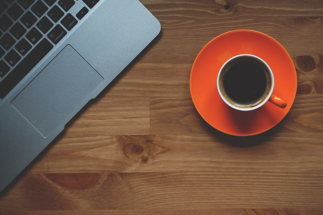 Laptop placed near cup of coffee on orange saucer