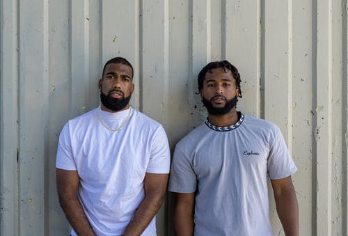 Two Men Standing beside the Gray Wall while Looking at Camera