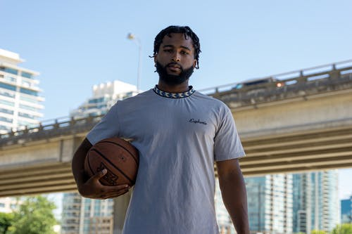Bearded Man in Gray Shirt Looking at Camera while Holding a Basketball