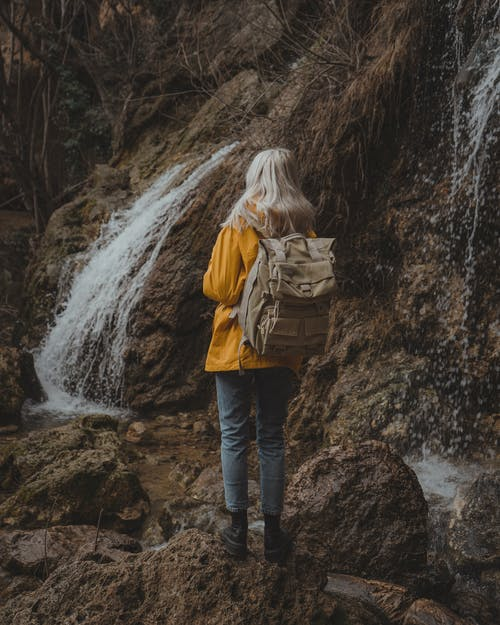 Back View of a Woman Carrying Backpack Standing on Rocks