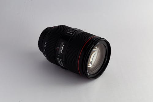 Close-Up Photo of Black Canon Dslr Camera Lens on White Surface
