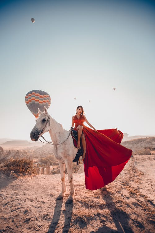 A Woman in Red Long Dress Sitting on a Horse