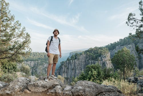 Man in Panama Hat Standing on Rock in Mountains