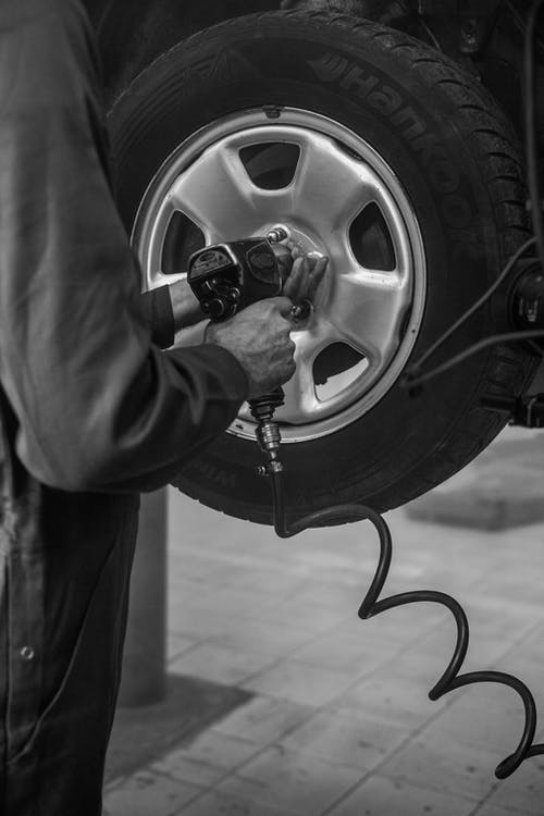 Grayscale Photo of Person Changing Car Tire With An Air Wrench
