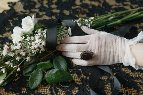Person in White Lace Gloves Holding White Flowers