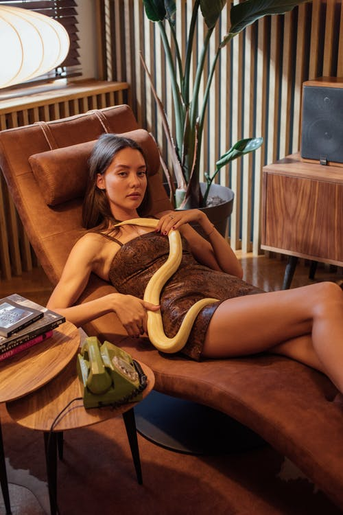 A Woman Lying Down With a Snake