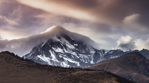 Snow Covered Mountains in Clouds