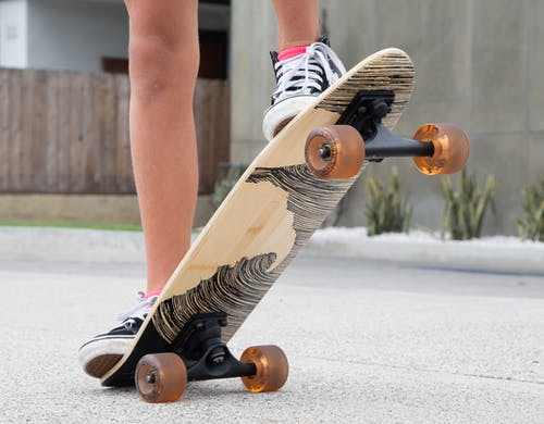 Person in Black and White Striped Pants and Black and White Nike Sneakers Riding Skateboard during