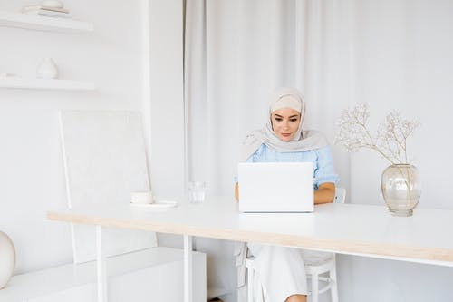 Woman in White Hijab Holding White Laptop Computer