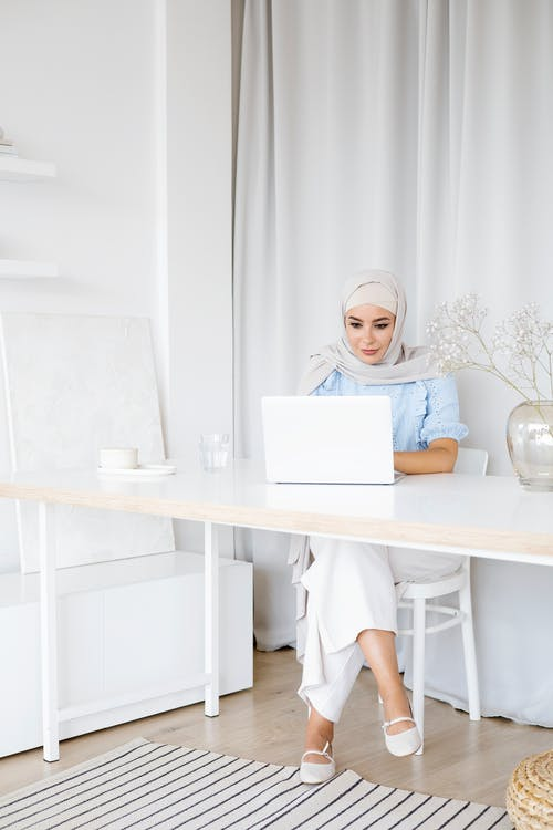 A Woman with Gray Hijab Using a Laptop while Sitting
