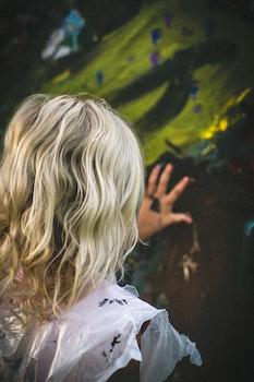 Girl in White Touching Brown Textile during Daytime