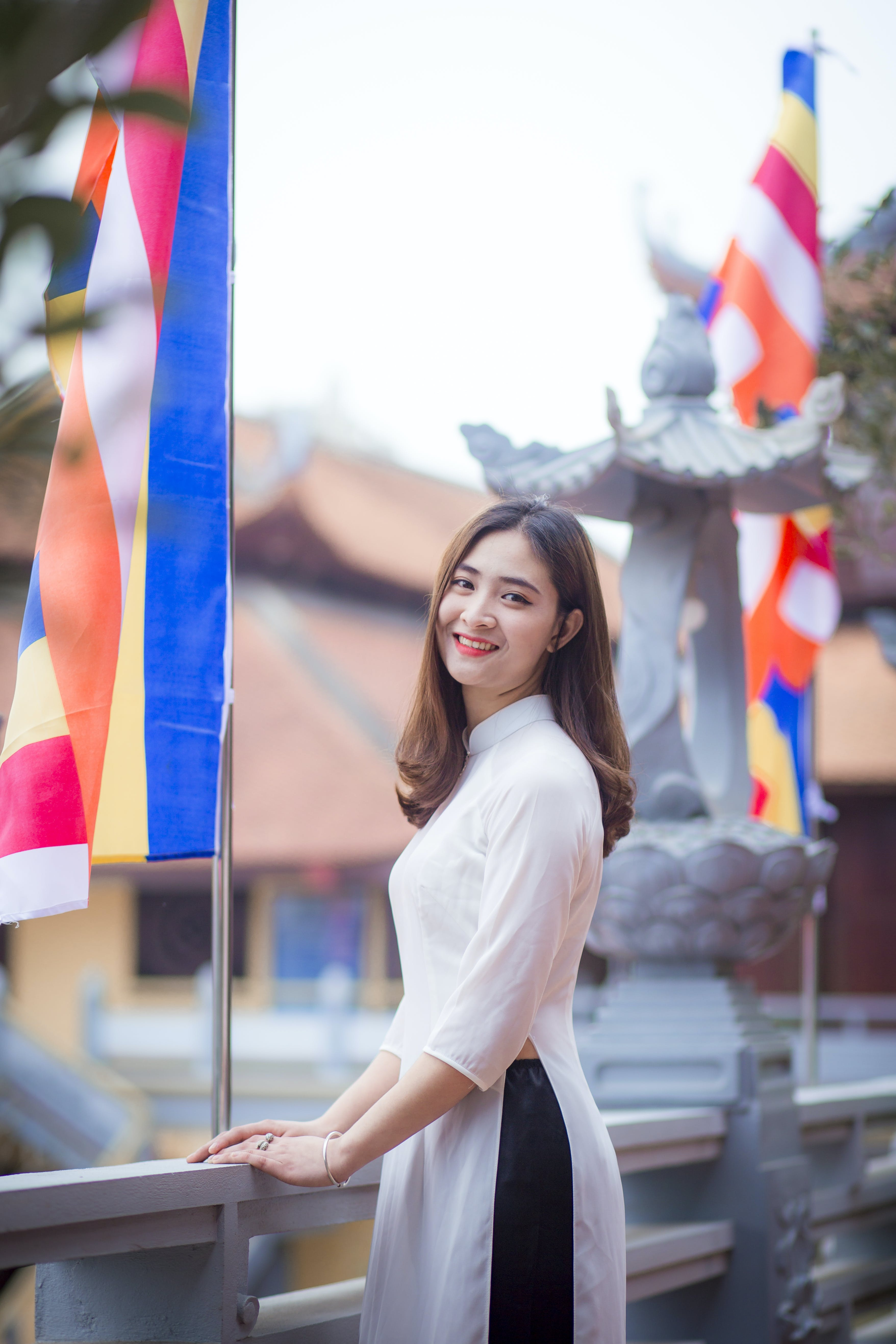 Depth of Field Photo of Woman Wearing White Dress Standing Near Flag Pole