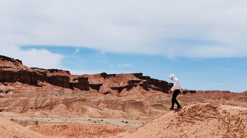 Man in White Shirt and Black Pants Standing on Brown Rock Formation