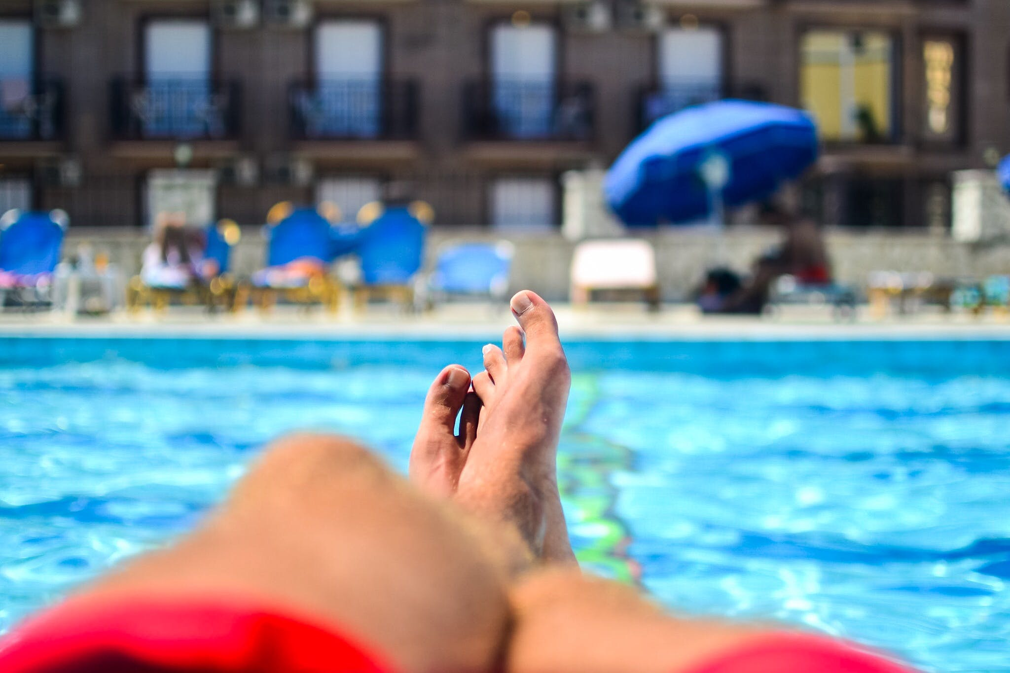 Person Lying in Front of Outdoor Pool