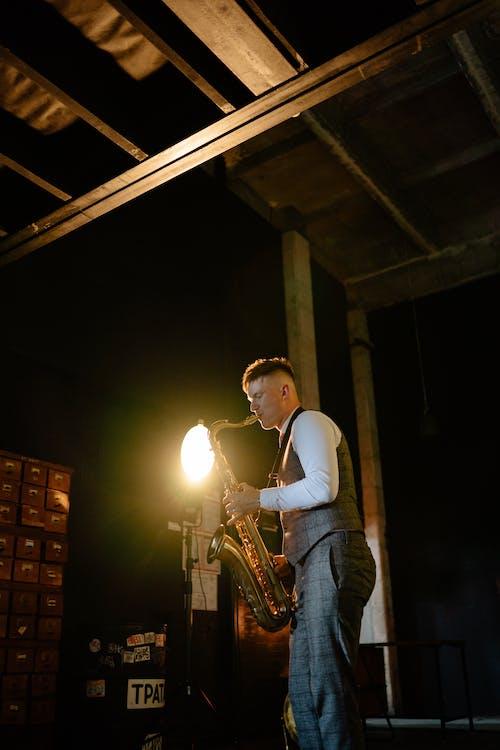 Man in White Shirt Playing Saxophone