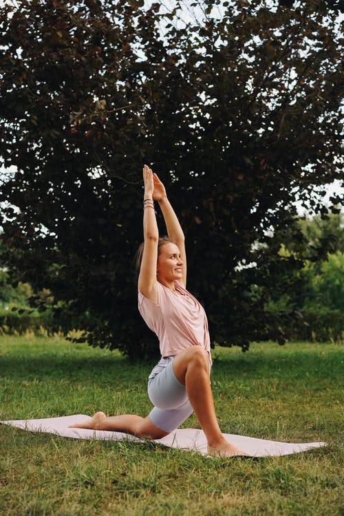 Photo of a Woman Doing Yoga on a Yoga Mat Outdoors