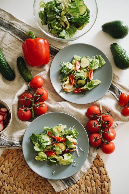 Salad on Gray Ceramic Plates Beside Vegetables on Table