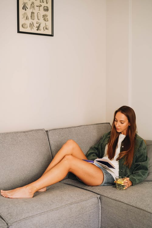 Woman Reading a Book on Her Living Room