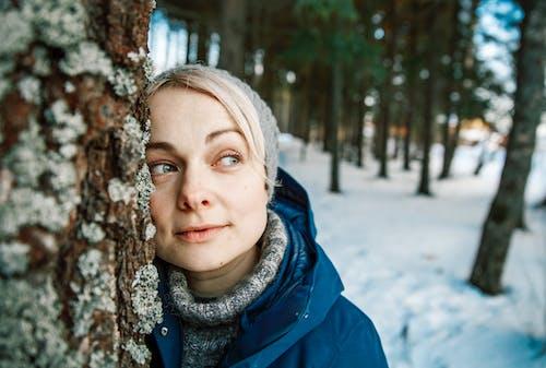 Woman in Blue Hoodie Standing Near Brown Tree