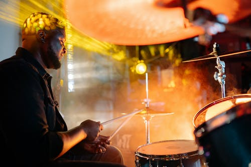 Man in Black Shirt Playing Drums Beside Yellow Light