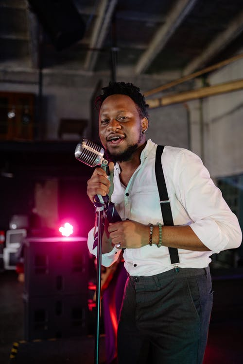 A Man Holding a Microphone and Singing