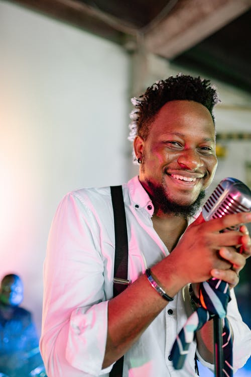 A Smiling Man Holding a Microphone