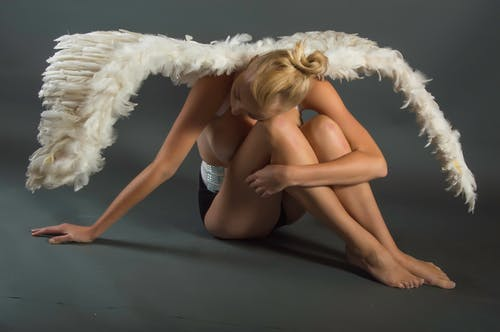 Woman Wearing White Angel Wings Sitting on Ground While Leaning Her Head on Her Knees